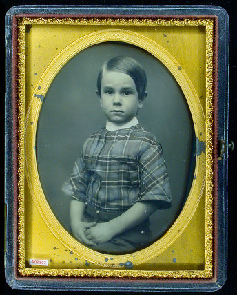 Portrait of an unidentified boy in a plaid tunic. [ca. 1854] quarter plate daguerreotype, some hand-tinting ; mat with protector 10.9 x 8.3 cm., case 11.8 x 9.3 cm.