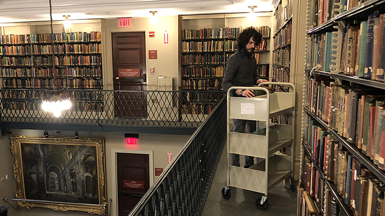 Reader Services staffer Arnold Serapilio reshelves books.