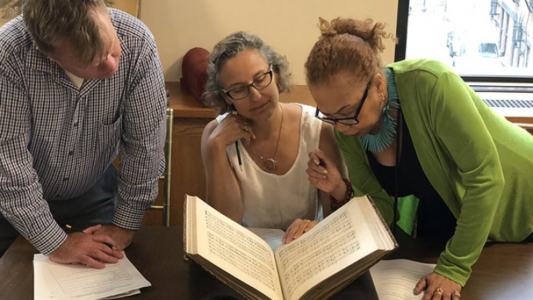 Three people huddled together to study a book that is open on a table.