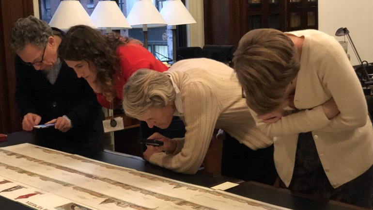 Four people studying a large document.