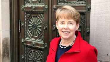 Smiling woman with short blonde hair in a red jacket stands in front of ornate bronze doors.