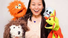 Smiling woman with long black hair surrounded by four puppets.