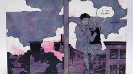 Front and back of a book binding depicting a young man and young woman larger than life sitting atop a building, hugging. A speech bubble over the woman says I love this part.